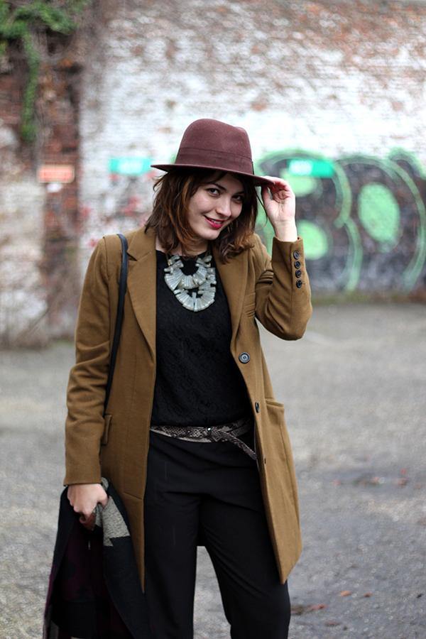 Hat, cognac coat, black jumpsuit & statement necklace