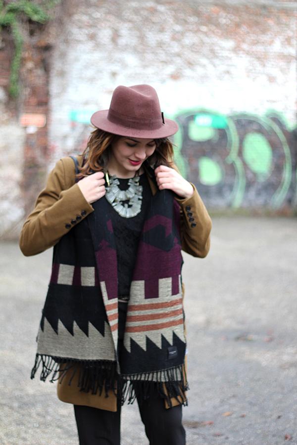 Hat, statement necklace, black jumpsuit, cognac coat